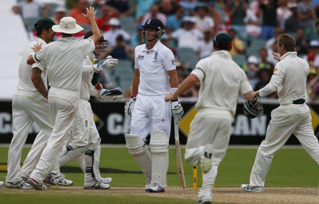 England's Joe Root (C) walks off the field after his dismissal as Australia's team celebrate during the fourth day's play in the second Ashes cricket test at the Adelaide Oval December 8, 2013. REUTERS/David Gray (AUSTRALIA - Tags: SPORT CRICKET)