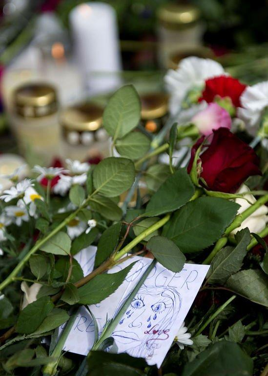 A drawing is left among the flowers at a memorial outside the Cathedral in Oslo. Business has never been so good, but the bumper takings are of little comfort to Norway's flower sellers as they struggle to keep pace with the demand from a nation in mourning