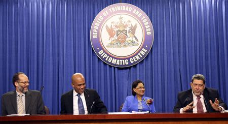Saint Vincent and the Grenadines' Prime Minister Ralph Gonsalves (R) addresses a media conference, with CARICOM Secretary-General Irwin LaRocque, Haitian President Michel Martelly, and Trinidad and Tobago's Prime Minister and chairperson of the Caribbean Community (CARICOM) Kamla Persad-Bissessar (L-2nd R) at the Diplomatic Centre, St Ann's, on the outskirts of the capital Port-of-Spain, November 26, 2013. REUTERS/Andrea De Silva