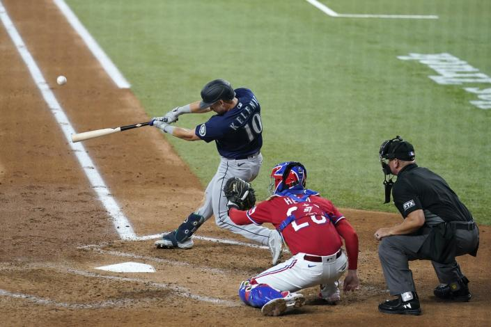 Seattle Mariners' Jarred Kelenic (10) connects for a three-run home run in front ot Texas Rangers' Jonah Heim and umpire Scott Barry during the third inning of a baseball game in Arlington, Texas, Friday, July 30, 2021. (AP Photo/Tony Gutierrez)