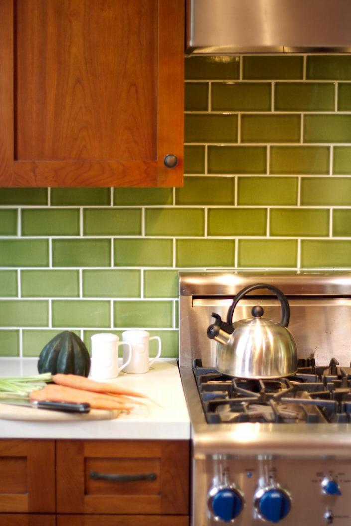 <p>An obvious way to add a personal touch to a subway tile backsplash is by ditching basic white and opting for a favorite color instead. In this Craftsman kitchen, the vibrant green backsplash contributes a cheery accent to the Shaker-style cabinets and stainless steel appliances. <i>Design by Kari McIntosh Dawdy.</i></p>