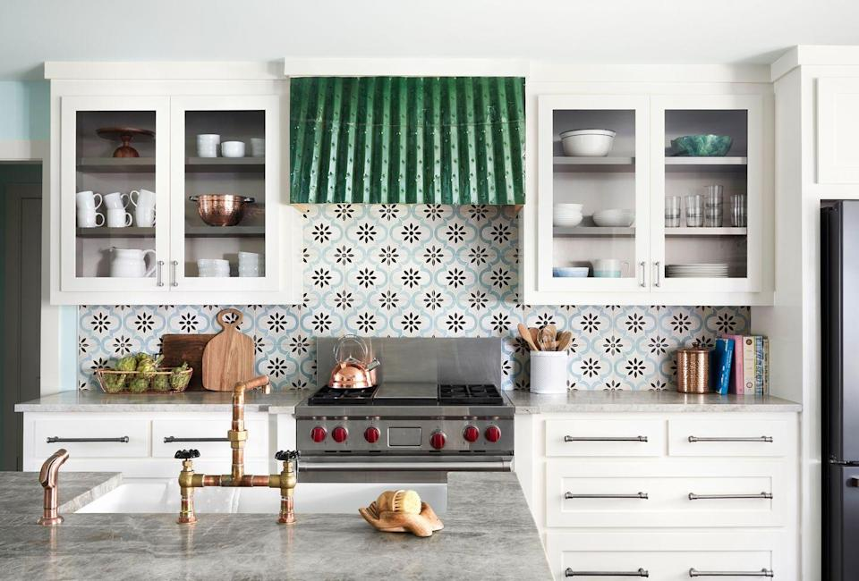 <p>Patterned tiles, along with a salvaged airplane part as a vent hood, bring a dose of drama to this kitchen. </p>