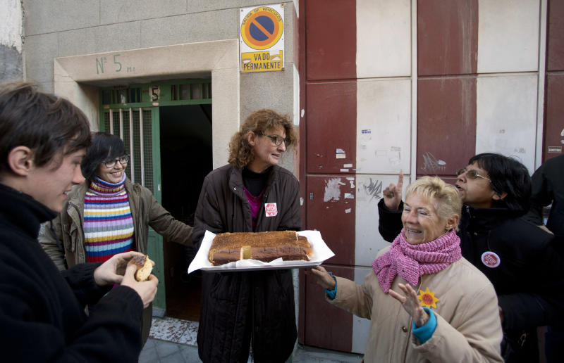 45-year old office manager Irene Gonzalez of Spain, centre offers cake to well-wishers, friends and journalists while she waits for her eviction from her home in Madrid, Monday Nov. 19, 2012. The police and court officials did not show up at the planned time and she still does not know if they will come later or on another day to evict her. Spain approved a two-year suspension of evictions Thursday for some needy homeowners unable to pay their mortgages, but activists said the government failed to address the larger issue of how those who give up their homes may still remain indebted, sometimes for the rest of their lives. Public attention on the issue intensified greatly in recent weeks after two homeowners facing eviction committed suicide. (AP Photo/Paul White)