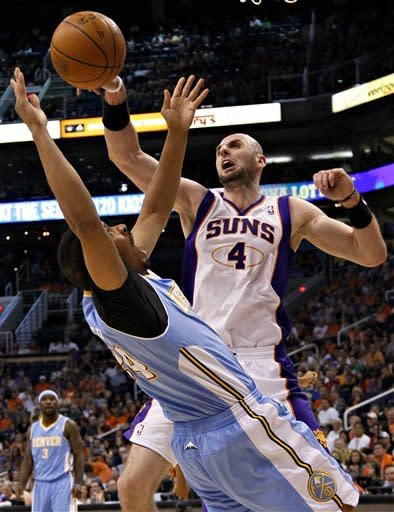 Phoenix Suns' Marcin Gortat (4), of Poland, blocks the shot of Denver Nuggets' Andre Miller during the first half of an NBA basketball game on Saturday, April 21, 2012, in Phoenix. (AP Photo/Matt York)