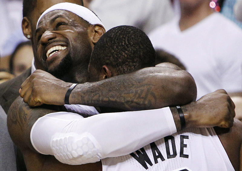 FILE - In this June 21, 2012 file photo, Miami Heat forward LeBron James, left, and guard Dwyane Wade embrace in the final moments of the second half of their 121-106 win over the Oklahoma City Thunder in Game 5 of the NBA Finals basketball series in Miami. As the NBA Most Valuable Player, Olympic champion, and, at long last, NBA champion, James, who was ripped by so many for leaving the Cleveland Cavaliers as a free agent and signing with Miami, cemented his position that he would never again be criticized for not winning the big prize. (AP Photo/Lynne Sladky, File)