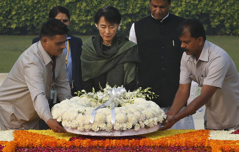 Myanmar's opposition leader and Nobel laureate Aung San Suu Kyi, center, pays respects at Rajghat, the memorial of Mahatma Gandhi, in New Delhi, India, Wednesday, Nov. 14, 2012. Suu Kyi is on a six-day visit to India. (AP Photo/Saurabh Das)