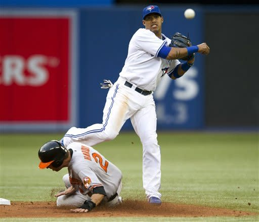 Toronto Blue Jays shortstop Yunel Escobar turns a double play on Baltimore Orioles' J.J. Hardy during the third inning of a baseball game, Wednesday, May 30, 2012, in Toronto. Orioles' Adam Jones was out at first. (AP Photo/The Canadian Press, Frank Gunn)