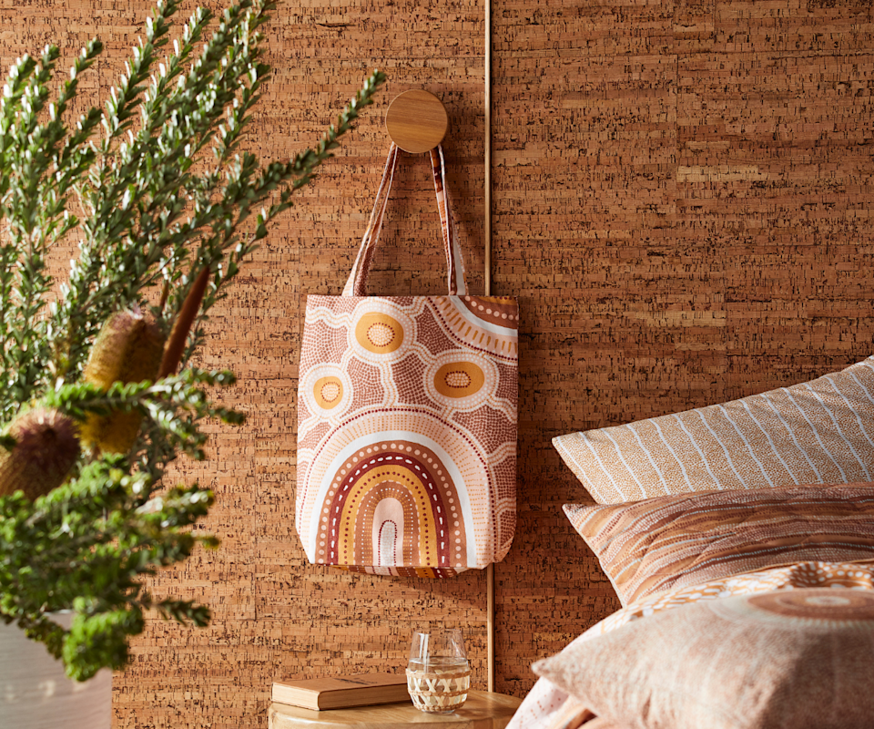 A patterned orange, red and pink tote bag in an indigenous print hangs on a brown wall next to a bed.