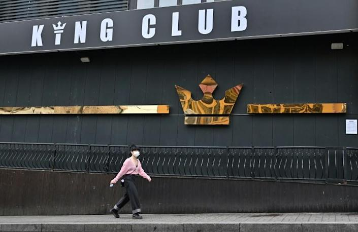 A woman wearing a face mask walks past a shuttered night club in Itaewon in Seoul (AFP Photo/Jung Yeon-je)