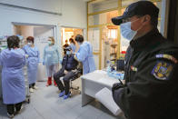 In this photo taken on Friday, Jan. 15, 2021 a Romanian gendarme waits to get a COVID-19 vaccine at a hospital in Bucharest, Romania. Across the Balkans and the rest of the nations in the southeastern corner of Europe, a vaccination campaign against the coronavirus is overshadowed by heated political debates or conspiracy theories that threaten to thwart the process. In countries like the Czech Republic, Serbia, Bosnia, Romania and Bulgaria, skeptics have ranged from former presidents to top athletes and doctors. Nations that once routinely went through mass inoculations under Communist leaders are deeply split over whether to take the vaccines at all. (AP Photo/Vadim Ghirda)