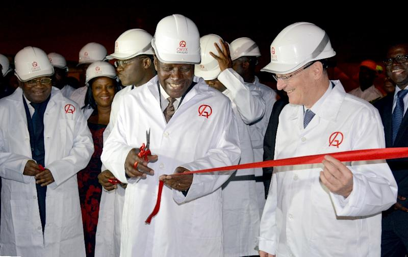 Ivory Coast Prime Minister Daniel Kablan Duncan (C) cuts the ribbon alongside Jean Claude Gandur, chairman of ORYX Energy, on new storage facilities at the ORYX Energy Cote d'Ivoire station, in the Vridi industrial zone, Abidjan, September 16, 2014 (AFP Photo/Issouf Sanogo)