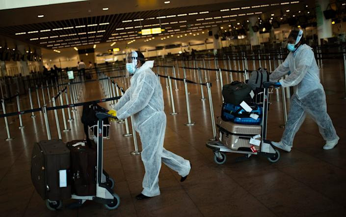 Passengers, wearing full protective gear to protect against the spread of coronavirus, push their luggage to check-in, as they check in to travel to Colombo, Sri Lanka, at the Zaventem international airport in Brussels, Wednesday, July 29, 2020. Europe's tourism revival is running into turbulence only weeks after countries reopened their borders, with rising infections in Spain and other nations causing increasing concern among health authorities over people bringing the coronavirus home from their summer vacations. (AP Photo/Francisco Seco) - AP
