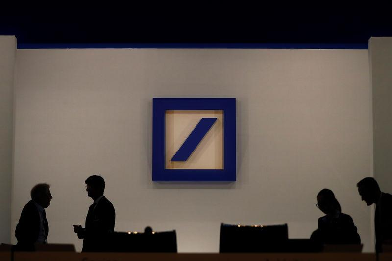 People are silhouetted next to the Deutsche Bank's logo prior to the bank's annual meeting in Frankfurt