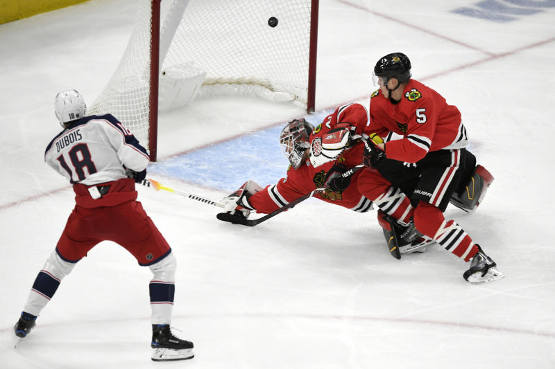 Columbus Blue Jackets' Pierre-Luc Dubois (18) scores a goal against Chicago Blackhawks goalie Robin Lehner (40), of Sweden, and Connor Murphy (5) during the second period of an NHL hockey game Friday, Oct 18, 2019, in Chicago. (AP Photo/Paul Beaty)