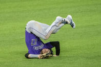 Colorado Rockies shortstop Trevor Story tumbles backwards on the turf after making a catch on a pop fly from Texas Rangers' Joey Gallo during the eighth inning of an opening day baseball game Friday, July 24, 2020, in Arlington, Texas. (AP Photo/Jeffrey McWhorter)
