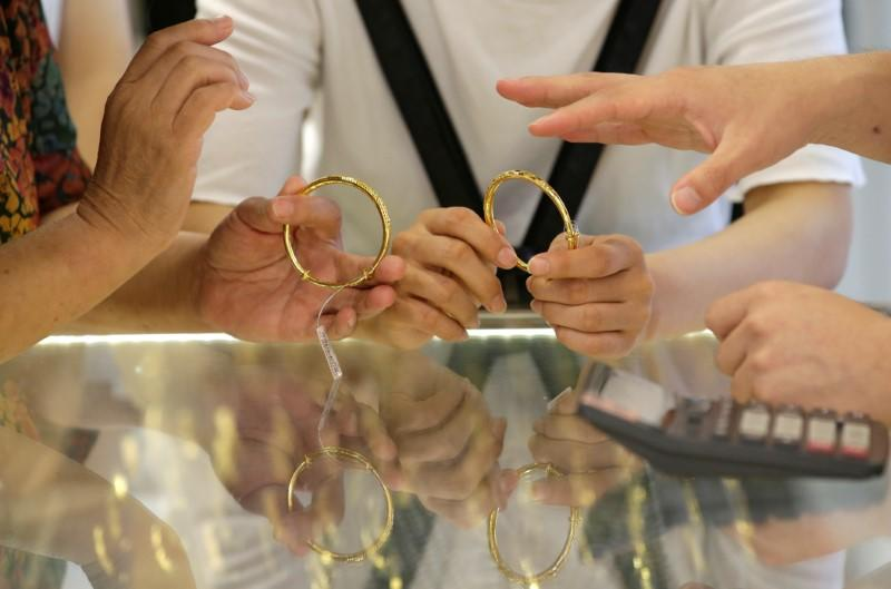 Gold falls 1% after hitting two-week high but stays above $1,550
