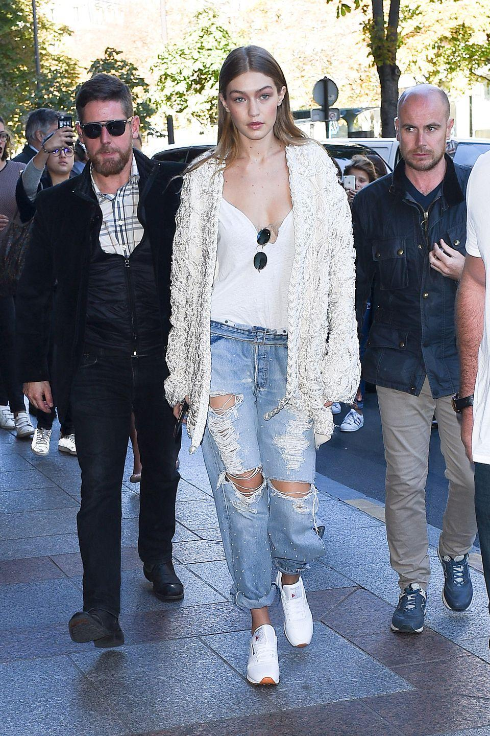 <p>In a pearl braided jacket by Jonathan Simkhai, white low-cut tee, round sunglasses, pearl-embellished ripped boyfriend jeans and white Reebok trainers while leaving the Miu Miu show in Paris.</p>
