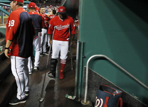 Washington Nationals left fielder Howie Kendrick walks on crutches in the dugout during the seventh inning of the second baseball game of a doubleheader against the Los Angeles Dodgers at Nationals Park, Saturday, May 19, 2018, in Washington. Kendrick injured his right Achilles tendon in the first game. The Dodgers won the second game 5-4. (AP Photo/Alex Brandon)