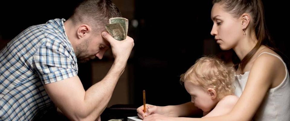 A family with a small child considers struggles with bills late in the evening.