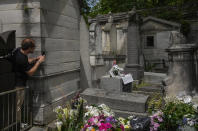 Didimi Sturua of Georgia takes a pictures with his cellphone of the tomb of rock singer Jim Morrison at the Pere-Lachaise cemetery in Paris, Saturday, July 3, 2021. Fans across Europe gathered at the grave of rock legend Jim Morrison to mark the 50th anniversary of his death. (AP Photo/Michel Euler)
