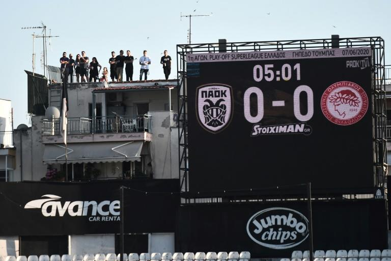 Roof dwellers: PAOK fans watch the Greek Super League game against Olympiakos above the Toumba stadium in Thessaloniki
