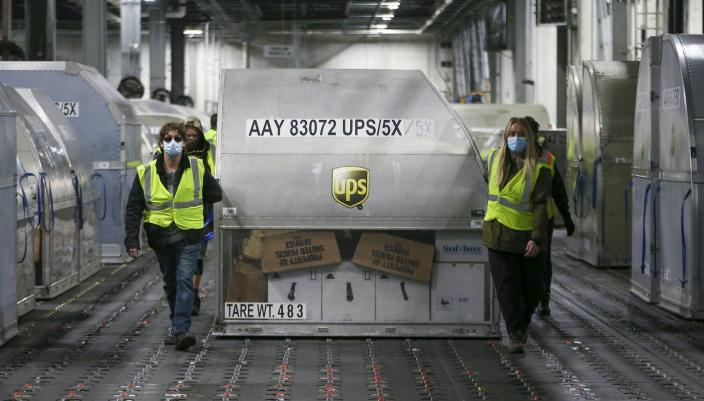 """<span class=""""caption"""">UPS employees roll out first doses of the Pfizer vaccine at the UPS hub in Louisville, Ky., on Dec. 13, 2020. </span> <span class=""""attribution""""><a class=""""link rapid-noclick-resp"""" href=""""https://www.gettyimages.com/detail/news-photo/employees-move-one-of-two-shipping-containers-containing-news-photo/1230114169?adppopup=true"""" rel=""""nofollow noopener"""" target=""""_blank"""" data-ylk=""""slk:Michael Clevenger/Getty Images"""">Michael Clevenger/Getty Images</a></span>"""
