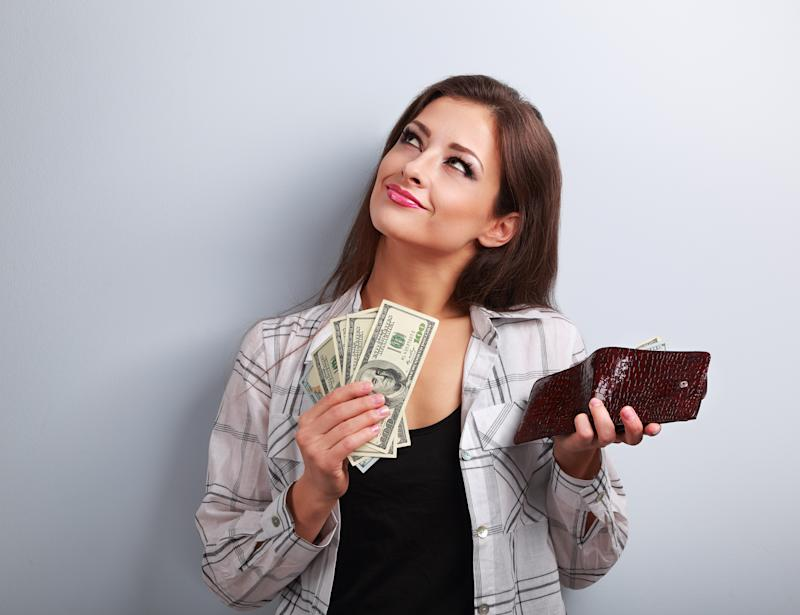 Thinking happy woman holding dollars and wallet in hands and want to spend money on blue background