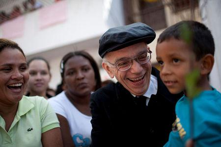 FILE PHOTO: Founder of the National System of Youth and Children's Orchestras of Venezuela Jose Antonio Abreu carries a child as he arrives at a free concert at the low-income neighborhood of La Vega in Caracas August 2, 2009.   REUTERS/Carlos Garcia Rawlins/File Photo