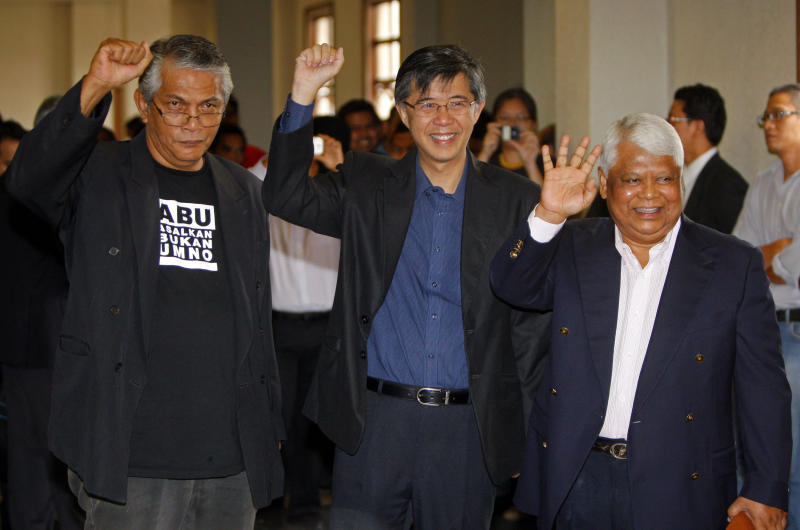 Social activist Haris Ibrahim, left, opposition leader Tian Chua, center, and Pan-Malaysian Islamic Party activist Tamrin Ghafar pose for photographers as they arrive at a court house in Kuala Lumpur, Malaysia, Wednesday, May 29, 2013. Prosecutors have filed sedition charges against another four opposition politicians and activists, including Ibrahim, Chua and Ghafar, who urged Malaysians to protest what they insist was a fraud-tainted victory by the ruling coalition in recent national elections. (AP Photo/Lai Seng Sin)