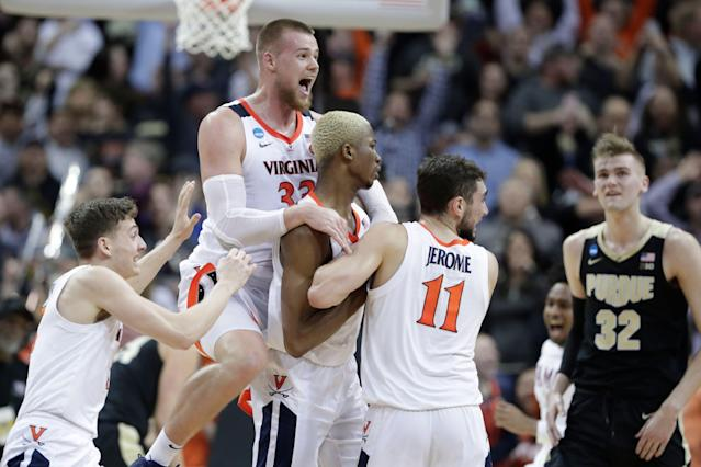 """Virginia's Jack Salt (33) celebrates with teammates <a class=""""link rapid-noclick-resp"""" href=""""/ncaab/players/133509/"""" data-ylk=""""slk:Mamadi Diakite"""">Mamadi Diakite</a> and <a class=""""link rapid-noclick-resp"""" href=""""/ncaab/players/136062/"""" data-ylk=""""slk:Ty Jerome"""">Ty Jerome</a> (11) as Purdue's Matt Haarms (32) watches after Diakite hit a shot to send the game to overtime of the men's NCAA Tournament college basketball South Regional final game, Saturday, March 30, 2019, in Louisville, Ky. (AP Photo/Michael Conroy)"""