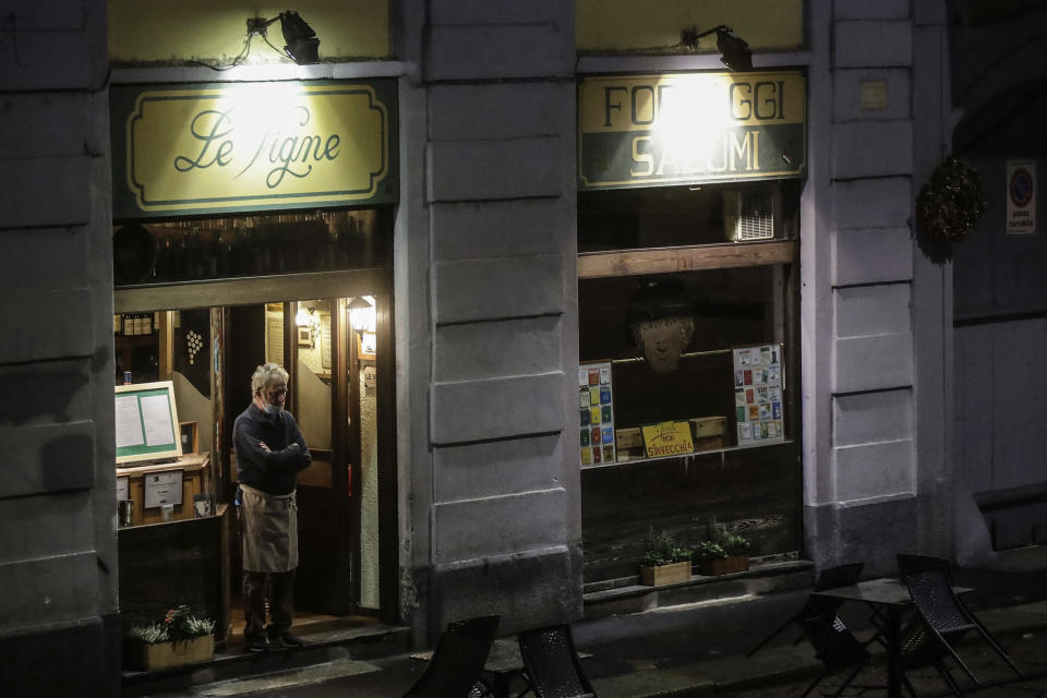 The owner of a restaurant stands in the doorway of the his establishment in the Naviglio Grande district, in Milan, Italy, Friday, Oct. 23, 2020. (AP Photo/Luca Bruno)