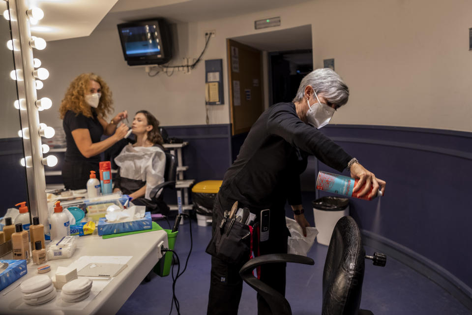 "A makeup artist disinfects a chair used by a cast member before a performance of ""Rusalka"" at the Teatro Real in Madrid, Spain, on Thursday, Nov. 12, 2020. The theater is one of the few major opera houses that have reopened during the coronavirus pandemic, although to smaller audiences. (AP Photo/Bernat Armangue)"