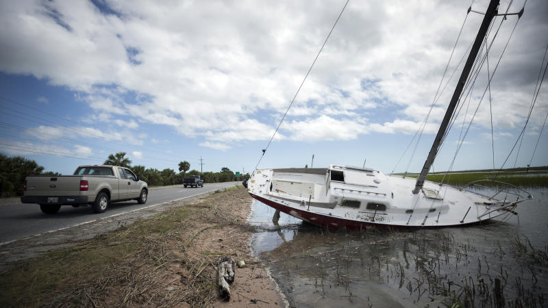 Residents drive past a sailboat washed onto the road to Tybee Island, Ga., Tuesday, Sept., 12, 2017, after the state opened Highway 80 after Tropical Storm Irma flooded island yesterday. (AP Photo/Stephen B. Morton)