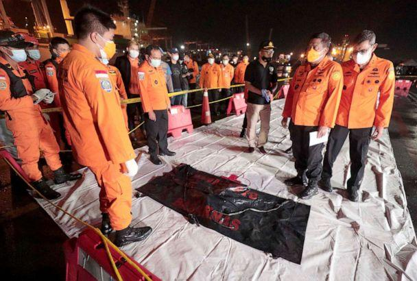 PHOTO:Members of the National Search and Rescue Agency Bagus Puruhito examine a body bag containing debris found in the water off Java Island, Jakarta, Indonesia, early Sunday, Jan. 10, 2021.  (Dita Alangkara/AP)