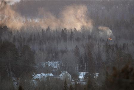 Flames and smoke are seen at the site of a train derailment in Wapske