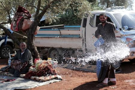 FILE PHOTO: A displaced Syrian pours water in an olive grove in the town of Atmeh, Idlib province, Syria