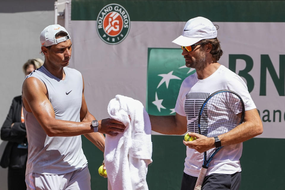 Spain's Rafael Nadal, left, takes his towel from coach Carlos Moya during a training session at Roland Garros stadium ahead of the French Open tennis tournament in Paris, Thursday, May 27, 2021. (AP Photo/Michel Euler)