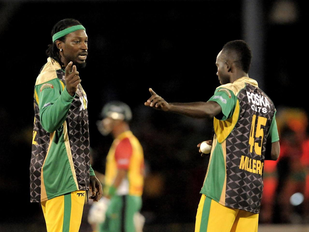 PORT OF SPAIN, TRINIDAD AND TOBAGO - AUGUST 24:  Captain Chris Gayle (L) of Jamaica Tallawahs sets the field for Nikita Miller (R) during the Final of the Caribbean Premier League between Guyana Amazon Warriors v Jamaica Tallawahs at Queens Park Oval on August 24, 2013 in Port of Spain, Trinidad and Tobago. (Photo by Randy Brooks/Getty Images Latin America for CPL)