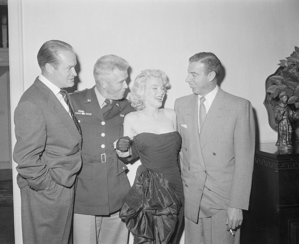 <p>Marilyn Monroe, her husband Joe DiMaggio, General William Dean, and Bob Hope laugh it up at a holiday party held at Hope's house on December 17, 1953. </p>