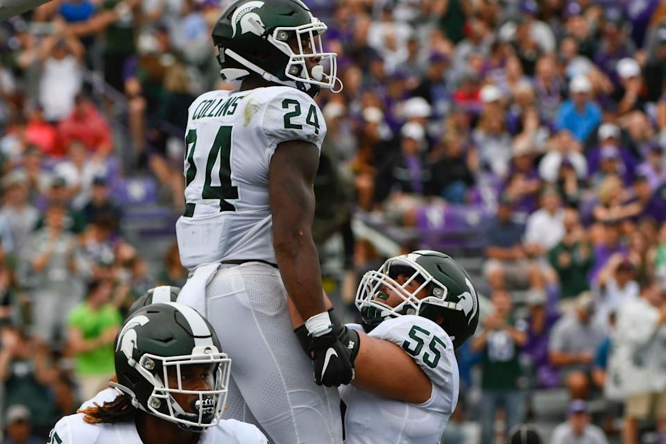 Michigan State offensive lineman Jordan Reid (55) lifts up running back Elijah Collins (24) after Collins scored a touchdown against Northwestern during the first half at Ryan Field, Saturday, Sept. 21, 2019, in Evanston, Ill.