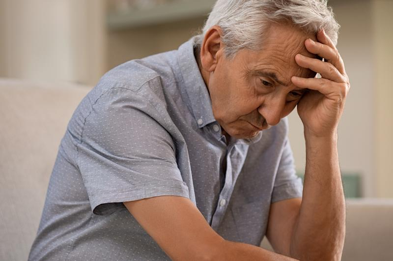 Older man with sad expression holding his head