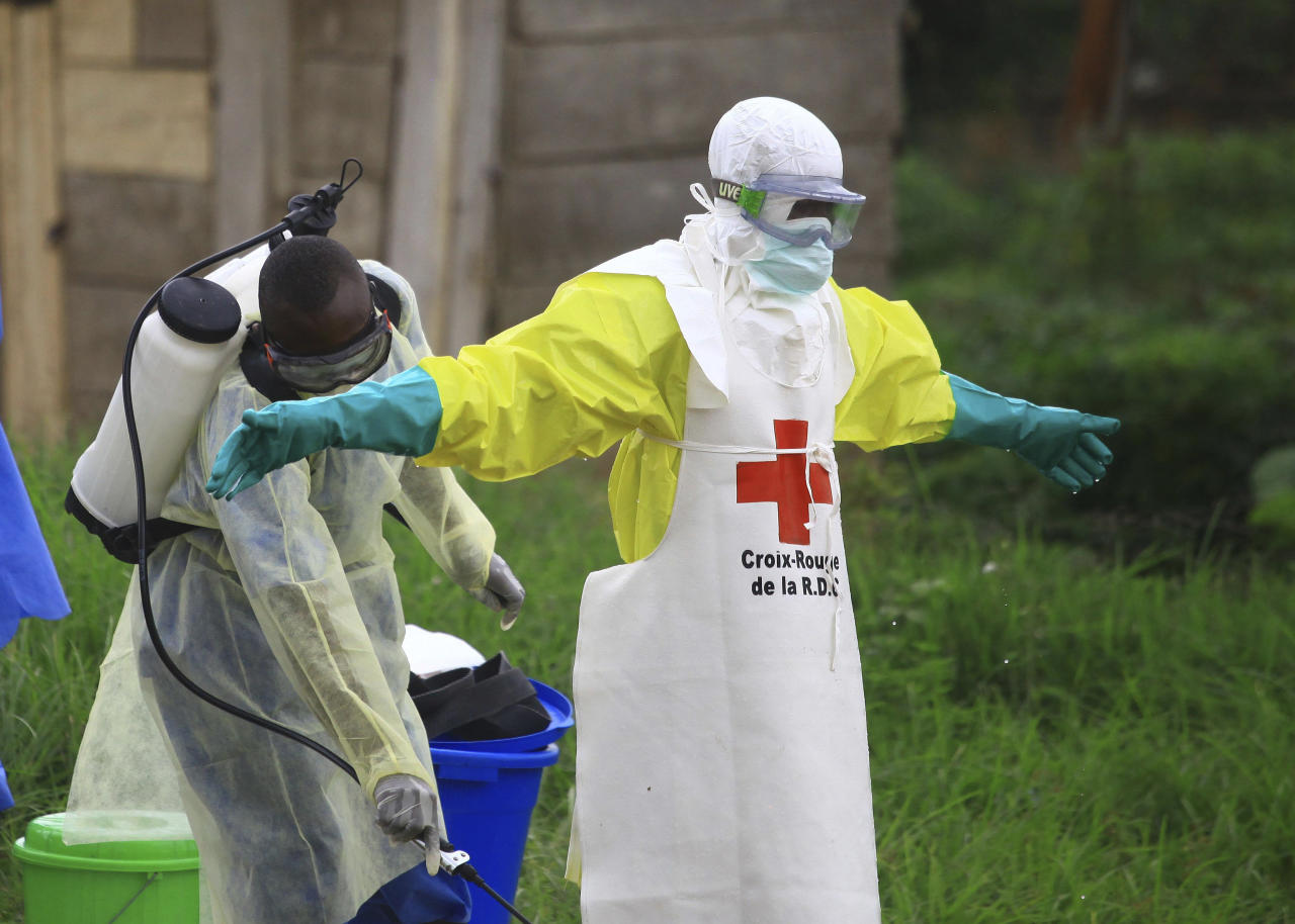 <p> FILE - In this Sunday, Sept 9, 2018 file photo, a health worker sprays disinfectant on his colleague after working at an Ebola treatment centre in Beni, Eastern Congo. Congo' military said Sunday Oct. 21, 2018, that rebels attacked an Ebola treatment centre in Beni, leaving 13 civilians dead and abducted a dozen children, which could force crucial virus containment efforts to be suspended in the area.(AP Photo/Al-hadji Kudra Maliro, FILE) </p>