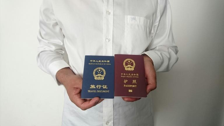 An unidentified Chinese Uighur man in the city of Medina holds his expired Chinese passport (red) and a one-way travel document (blue) issued in its place by the Chinese mission in Saudi Arabia
