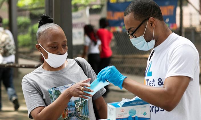 Stephane Labossiere, right, with the Mayor's Office of Immigrant Affairs, hands out masks and printed information about free coronavirus testing in Brooklyn offered by NYC Health + Hospitals in New York.