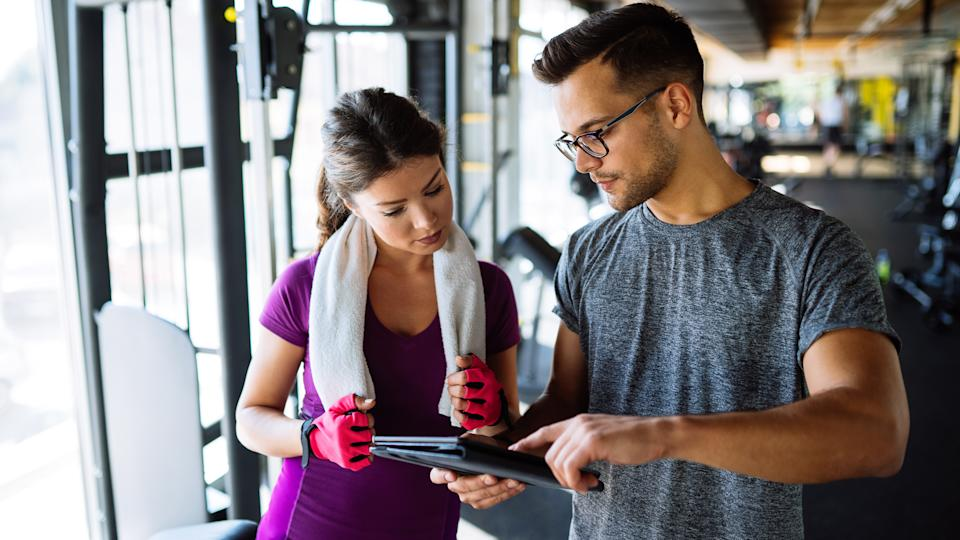 Woman and personal trainer making exercise plan in gym.