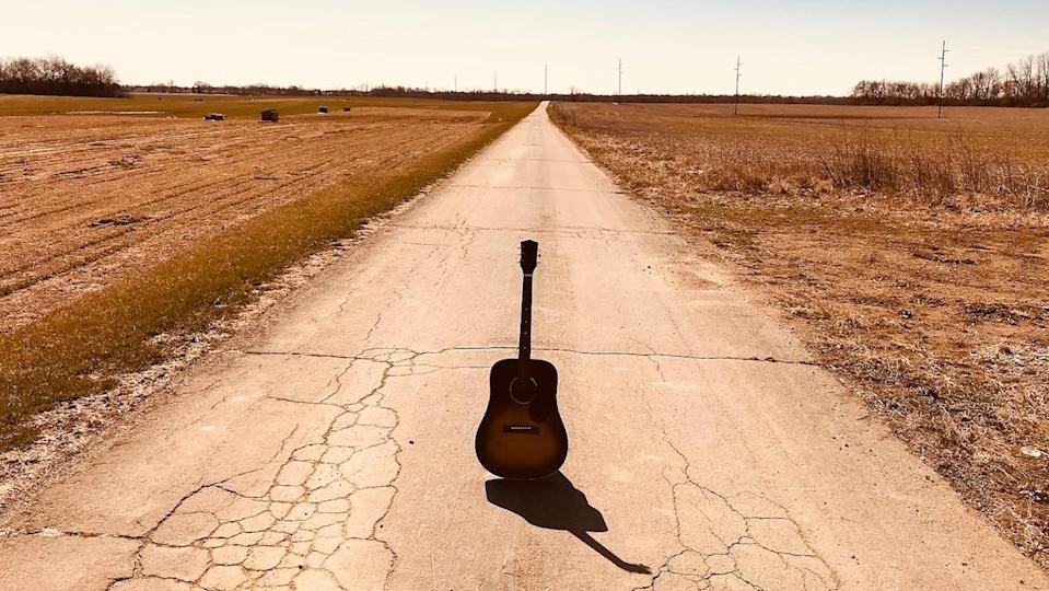 A lone acoustic guitar sits in the middle of an old deserted road out in themiddle of nowhere during the day
