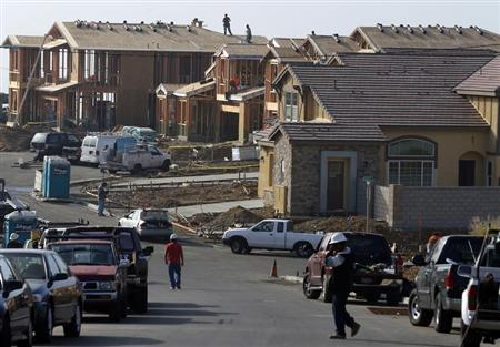 People walk near new single family homes under construction in San Marcos