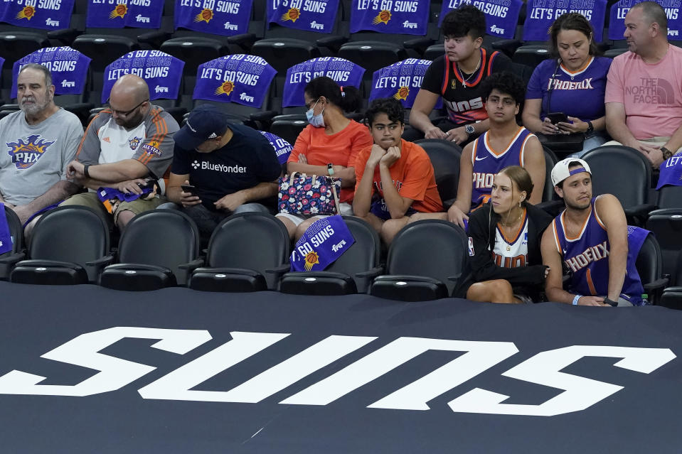 Fans watch players warm up before Game 2 of the NBA basketball Western Conference Finals between the Phoenix Suns and the Los Angeles Clippers, Tuesday, June 22, 2021, in Phoenix. (AP Photo/Matt York)