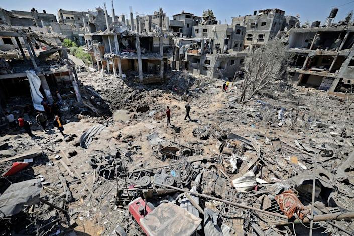 A few people walk amid the rubble of flattened and severely damaged buildings.