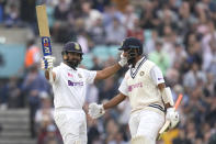 India's Rohit Sharma, left, celebrates scoring 100 runs with batting partner India's Cheteshwar Pujara on day three of the fourth Test match at The Oval cricket ground in London, Saturday, Sept. 4, 2021. (AP Photo/Kirsty Wigglesworth)